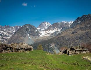 alpeggio con baite e sfondo di montagne