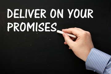 Writing Deliver On Your Promises on a Blackboard