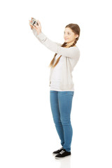 Teen woman making photo with camera.