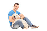 Cheerful young man posing with a cute little puppy
