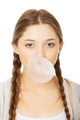 Teen woman making balloon with gum.