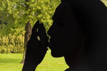Composite image of asthmatic brunette using her inhaler