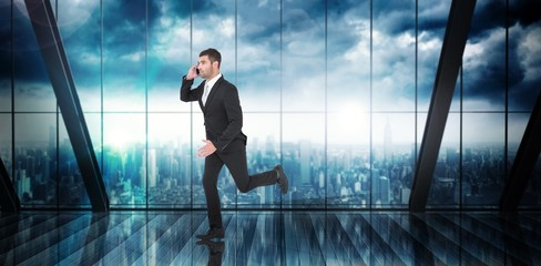 Composite image of businessman running on the phone