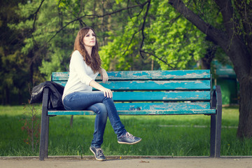 Young beautiful woman sitting on bench in park