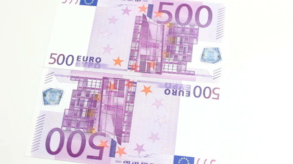 Two 500 euro notes rotating on white background