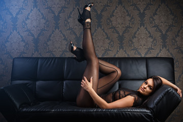 Sexy woman on a leather sofa