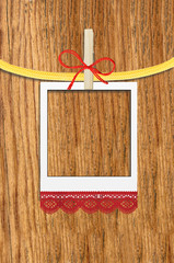 empty photo frame with clothespin over wooden background