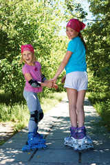 Two girls in roller skates looking at the camera.