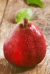 Fresh red pear with drops of water on wooden table, selective fo