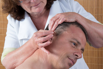 Woman  prepares to tap needle around ears of man