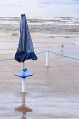 Folded umbrellas on the beach during a storm