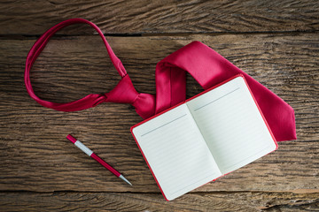 note book, pen, red necktie on grungy wooden surface