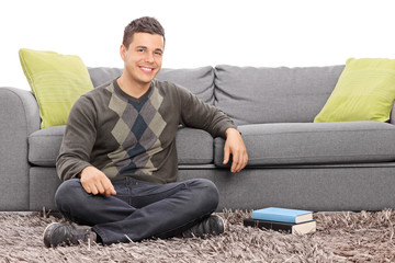 Relaxed young guy sitting on the floor