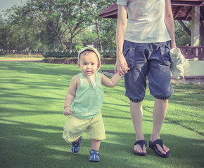 Mother hold baby hand walking on  grass field at out door park.