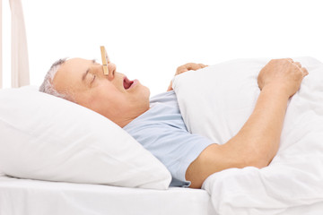 Senior sleeping with a clothespin on his nose