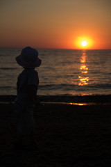 little boy standing back and enjoy the sunset on the sea