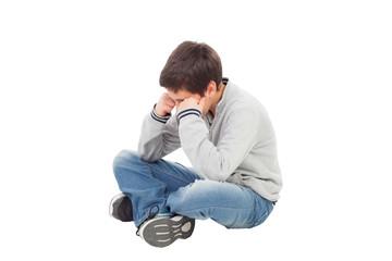Sad preteen boy sitting on the floor