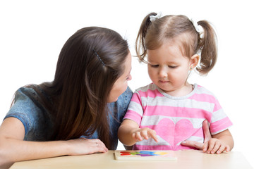 child and mother playing together with puzzle toy