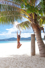 Girl jumping under palm tree
