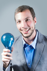 Handsome young smart man holding a blue light bulb