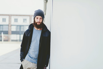 Serious Man in Winter Outfit Leaning on Wall