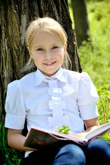 Cute little girl  sitting in the grass near a tree  with book