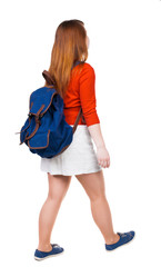 back view of walking  woman in dress with backpack.