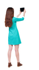 back view of standing young beautiful  girl with tablet computer