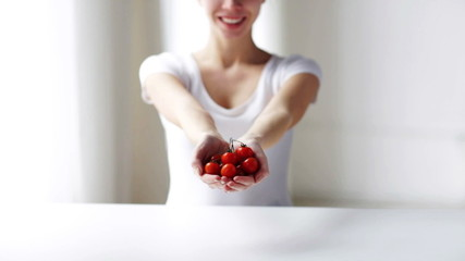 close up of young woman showing cherry tomatoes