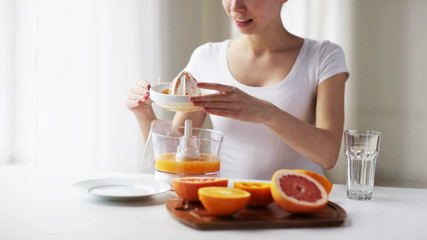 woman with squeezer pouring orange juice to glass