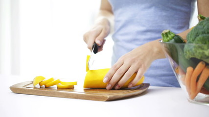 close up of young woman chopping squash at home