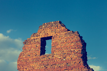 Fragment of ancient ruined building with window on blue sky back