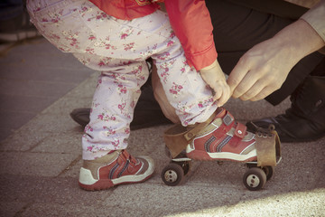 Old roller skates for infant girl. Old photo film styled picture