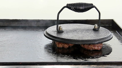 Fried ground beef patties on a sizzling skillet