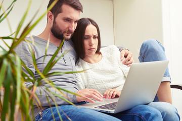 couple holding laptop