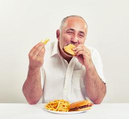 ddle-aged man eating burger