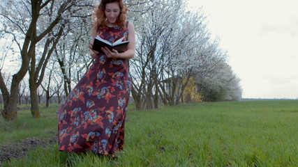 Girl in dress standing Turns the page diary on windy green field