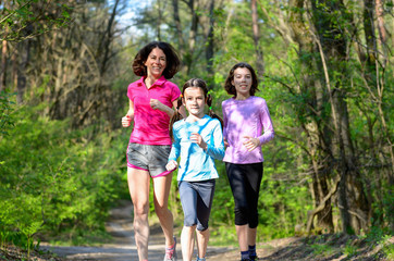 Family sport, mother and kids jogging, running in forest
