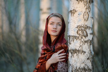 Russian girl in a scarf in a birch forest, close-up