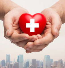 male hands holding red heart with white cross