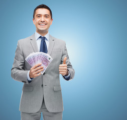 smiling businessman with money showing thumbs up