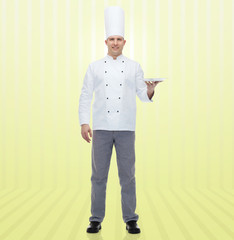 happy male chef cook showing empty plate