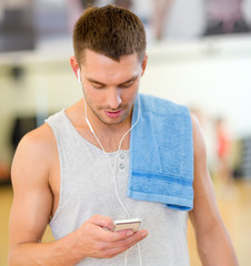 young man with smartphone and towel in gym