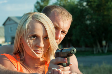 Young man is teaching his girlfriend to shoot by pneumatic handg