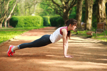Sportive girl working out doing push ups press exercise