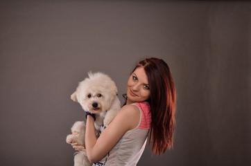 Teenage girl holding Maltese puppy