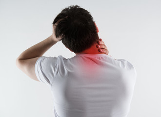 Young male massaging his neck in pain. Nape injury.