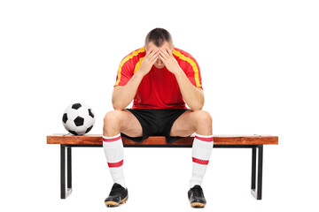 Worried young football player sitting on a bench