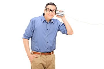 Cheerful young man talking through a tin can phone