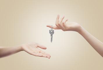 Mani con chiavi sfondo beige